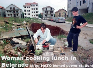 WOMAN PREPARES A MEAL OUTSIDE APARTMENT BLOCK IN BELGRADE.