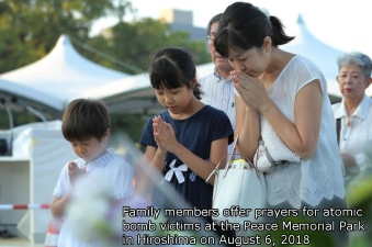 Family members offer prayers for the atomic bomb victims at the Peace Memorial Park in Hiroshima on August 6, 2018. A US B-29 plane dropped a bomb over the city at 8:15am on August 6, 1945, marking the first use of an atomic weapon which ultimately claimed the lives of some 140,000 people. / AFP PHOTO / JIJI PRESS / JIJI PRESS / Japan OUTJIJI PRESS/AFP/Getty Images